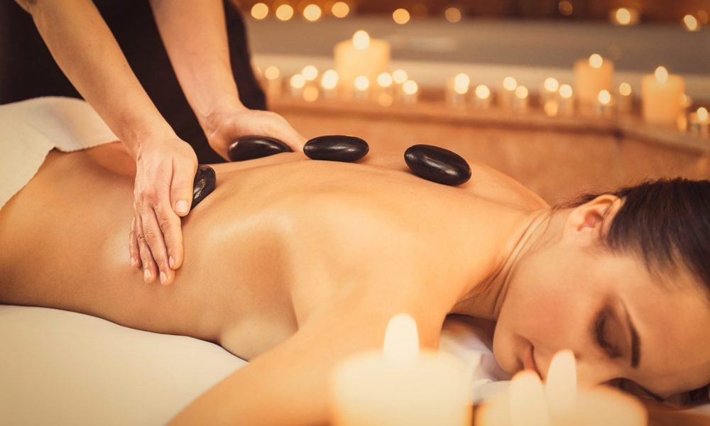 Serene young woman is enjoying massage at beauty salon. Masseuse is touching hot smooth stones to her body